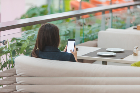 woman with phone sitting in cafe. surfing in internet. copy space. white screen Banque d'images - 119524497