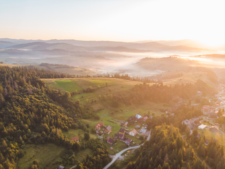 aerial view of sunset over mountains with forest and village. summer time