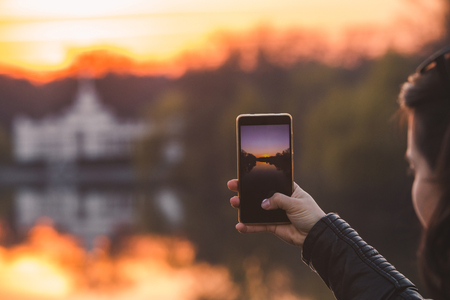woman taking picture of sunset on her phone. lifestyle concept