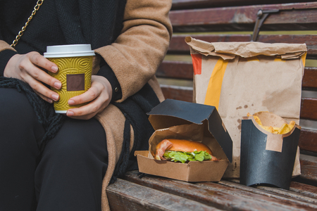 woman hands close up holding burger with coffee cup. fast food concept