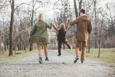 young beautiful family walking holding hands by city park. autumn season