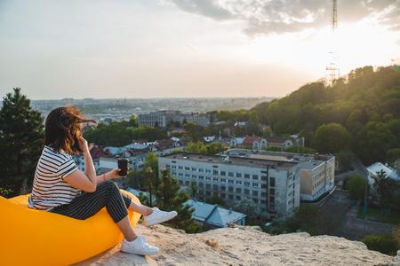 一个女人坐在黄色的充气床垫上喝咖啡,欣赏城市的日落。本空间
