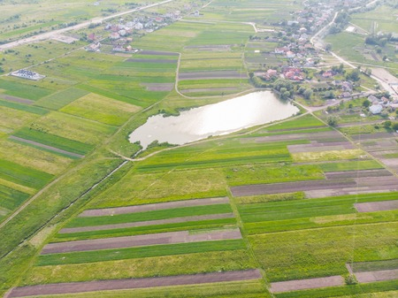 aerial view of fields with village near it. summer landscape
