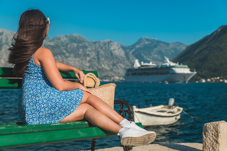 beautiful woman on bench sea and mountains on background. summer vacation. cruise liner