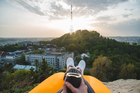 woman looking at sunset over city. drinking coffee. sitting on the peak