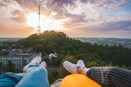 couple laying and enjoying view of sunset over the city. romantic date