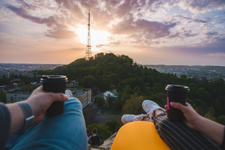 couple laying and enjoying view of sunset over the city. drinking coffee romantic date