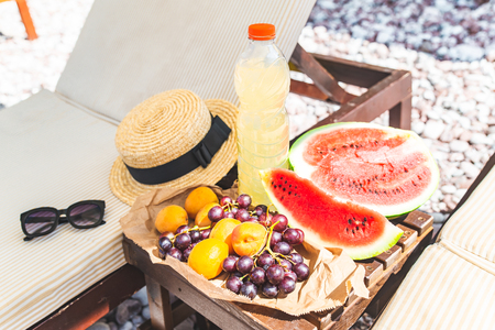 picnic at the beach. fresh fruits on the table near sun loungers. summer vacation Imagens