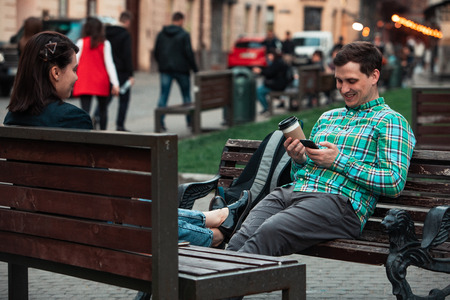 laughing talking man with woman sitting on bench drinking coffee surfing in internet. urban lifestyle. two persons