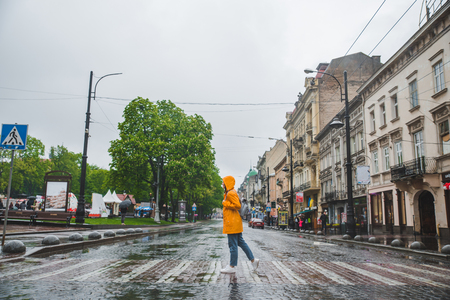 woman in the middle of the street crossing road in yellow raincoat. urban casual clothes Imagens