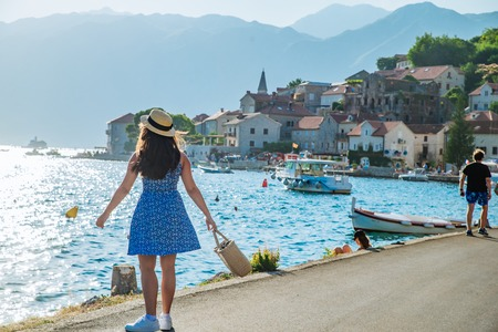young pretty stylish woman walking by city quay. sea and mountains on background. summer travel concept Imagens