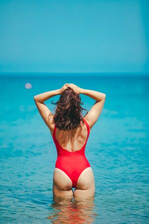 woman standing in sea in the middle in red swimming suit. view from behind. sexy ass. summer vacation