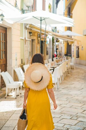 woman in yellow dress walking by resort city street between cafe restaurant tables. vacation concept Imagens