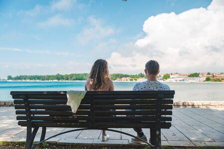 pareja de viajeros sentados en un banco con vista al mar descansando en la sombra. caluroso día de verano Foto de archivo