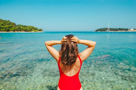 sexy woman in red swimsuit walking into blue clear sea water. summer vacation Stock Photo - 127823975