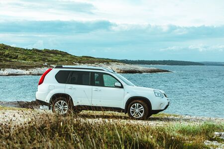white suv car at rocky seaside. off road car travel concept. summer vacation
