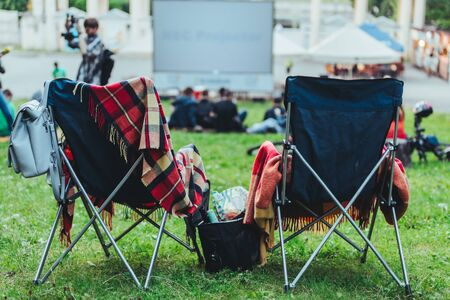 two folding chairs with cooling bag with beer and snacks in open air cinema copy space 版權商用圖片