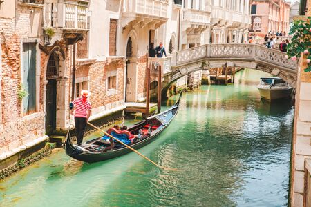 Italy, Venice - May 25, 2019: people at gondola taking tour by canal summer vacation