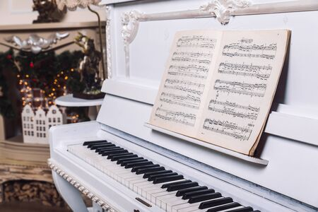 white piano with book with notes on it