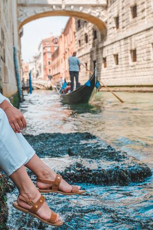 woman sitting at city quay at venice italy enjoying the view of canals with gondolas
