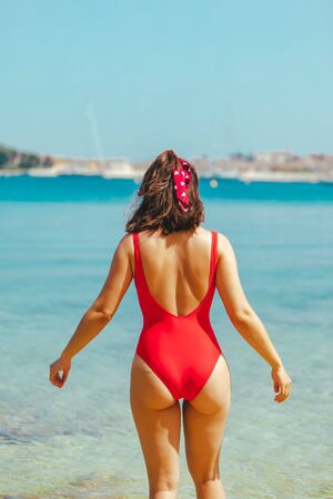 sexy woman in red swimsuit walking into blue clear sea water. summer vacation