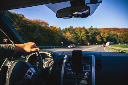man hands on steering wheel riding by autumn speedway fall season car travel Reklamní fotografie