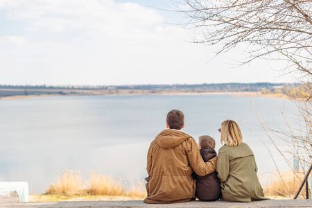 young beautiful family sitting at beach with view lake. autumn season