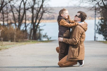 father hugging little son outdoors in park. autumn season