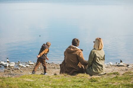 family walking near water. sitting at the beach. little kid throwing rock in water. resting time
