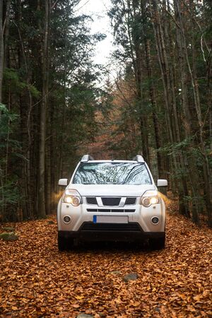 white suv car at trail road in autumn forest copy space lifestyle Foto de archivo - 130174162