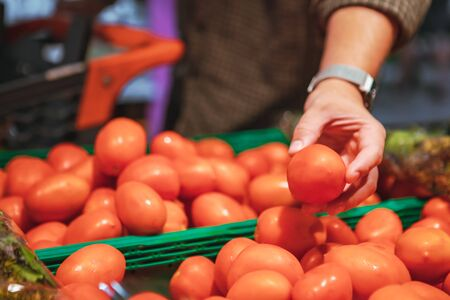 man hand choosing red tomatoes in grocery store shopping concept