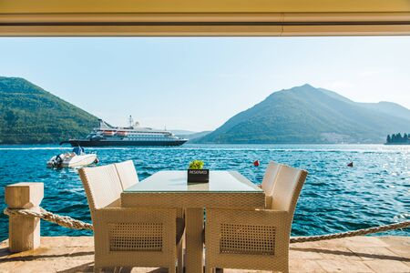 cafe table on beach with beautiful view of sea and mountains. reserved plate on it. cruise liner on background. summer travel concept