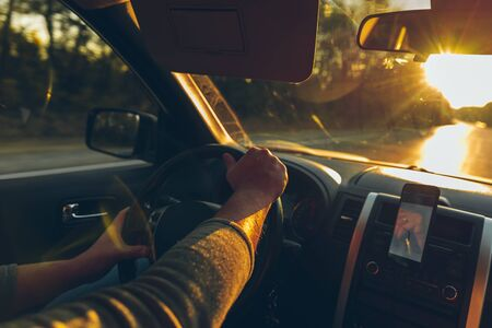 road trip concept man hands on steering wheel navigation on the phone autumn fall season
