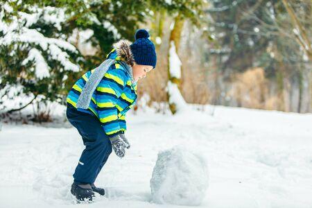 little cute boy making snowman. rolling big snowball Banque d'images