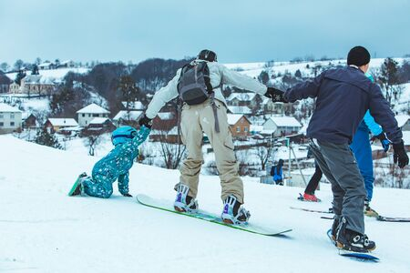 mother teaching little girl to snowboarding. lifestyle. winter activities