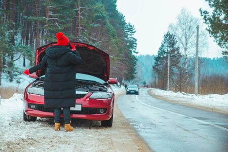 woman calling for help with broken down car at winter highway stopped at roadside