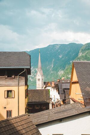 hallstatt church with bell tower lake with alpine mountains on background summer time