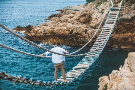 man walking by suspension bridge cross sea bay rocky cliff summer time