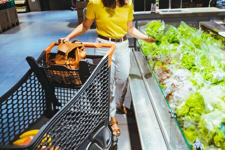 woman taking salad from grocery shopping store shelf supermarket