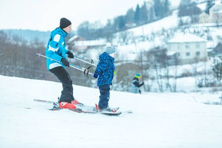 little boy holding sticks of the instructor. learning skiing. winter activities Banco de Imagens
