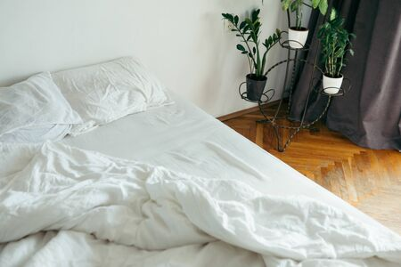 bed with white sheets close up bright morning light copy space