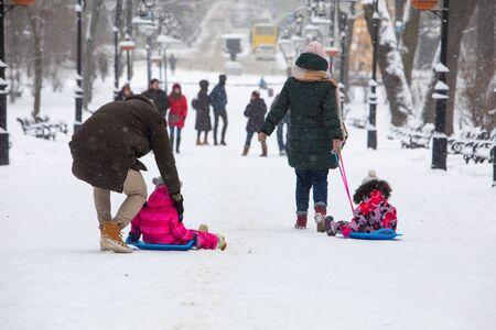 kids sliding at winter hill at city park parents pushing having fun