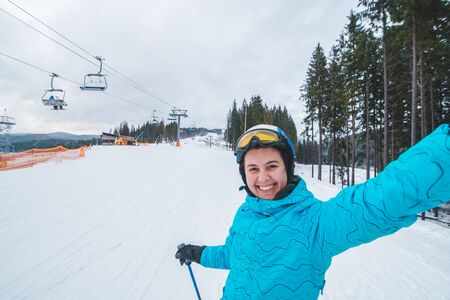 young pretty woman making selfie while skiing.