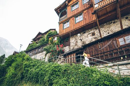 young pretty smiling tourist woman walking by small hallstatt street stairs Banco de Imagens