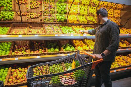 man in grocery store do shopping buying fruits Banco de Imagens
