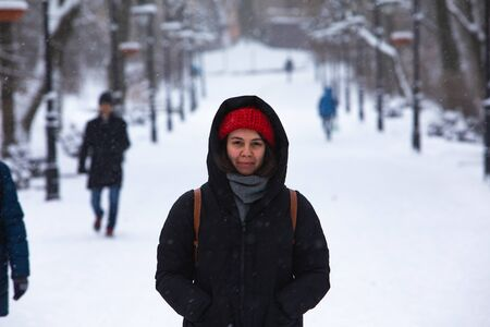 smiling woman portrait in winter outfit at city park