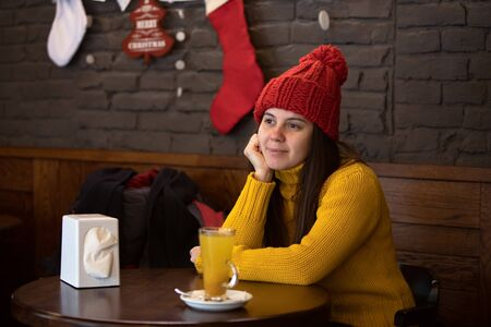 young happy woman in red hat winter outfit sitting in cafe drinking warm up tea