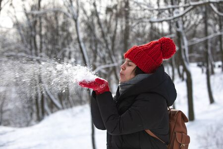 young pretty smiling woman in winter coat with red hat at city forest park