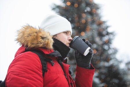 man outdoors drinking coffee from paper cup winter time warm up