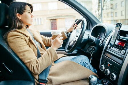 young pretty woman driving car while drinking cup of coffee